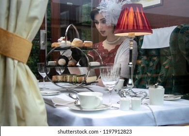 Vintage, beautiful woman in red afternoon tea dress enjoying afternoon tea in train carraige with cakes, sandwiches and tea