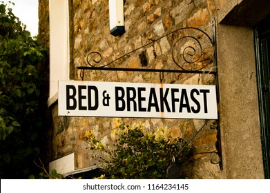 Vintage Bed & Breakfast Sign Attached To Rustic Brick Building In English Village