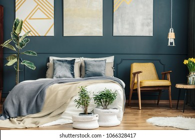 Vintage bedroom interior with retro chair, blue and grey blankets, cushions, plants, white carpet and modern paintings