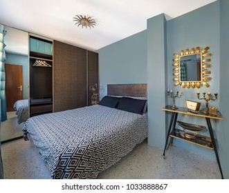Vintage bedroom with retro decoration with a edgy 50s clock, mirror, table and chandeliers. Big wooden wardrobe and geometric pattern duvet cover.