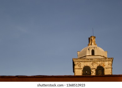 vintage bell tower on a bright blue sky background, bright orange walls