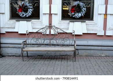 Vintage bench on the street. Chtistmas decoration on the house.
