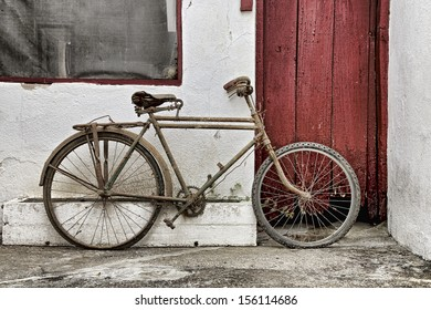 vintage bicycle against old building with wooden door