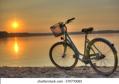 Vintage bicycle with a basket near the lake during beautiful summer sunset. Copy space