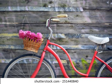 Vintage bicycle with basket with peony flowers near the old wooden wall