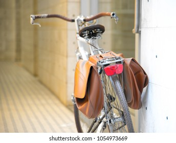Vintage bicycle with brown pannier bags for luggage parking on the street. Selective focus. Italy, Rimini