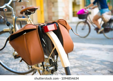 Vintage bicycle with brown pannier bags for luggage parking on the street. Selective focus on foreground.  People on background. Italy, Rimini