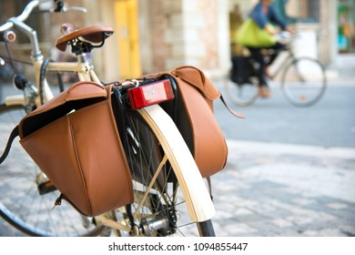 Vintage bicycle with brown pannier bags parking on the street. Selective focus on foreground.  People on background. Italy, Rimini. Italian lifestyle
