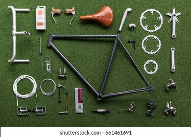 Vintage bicycle frame and parts laid out on a green mat ready for assembly