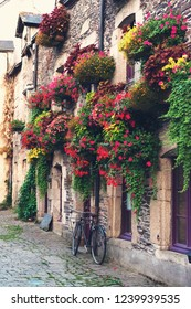 Vintage bicycle in front of the old rustic house, covered with flowers. Beautiful city landscape with an old bike near the stone wall with flowers in drawers in France, Europe. Retro style.