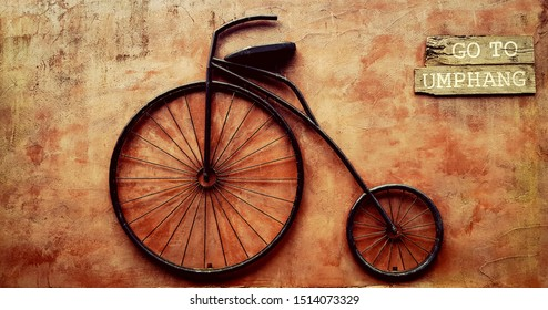 Vintage bicycle hanging on brown rough wall. Retro object and Decoration place
