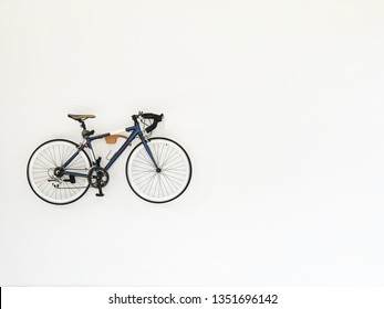 Vintage bicycle hanging on white wall for decoration