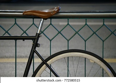 Vintage bicycle leaning against iron railings bar on street side at night