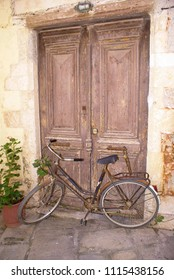 Vintage Bicycle Leaning against old door in Chania city, Greece