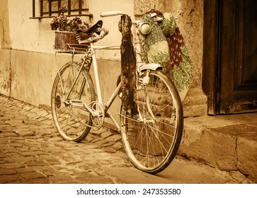 Vintage bicycle leaning against an old door in a medieval street