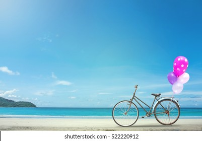 vintage bicycle on white sand beach over blue sea and clear blue sky background, spring or summer holiday vacation concept.