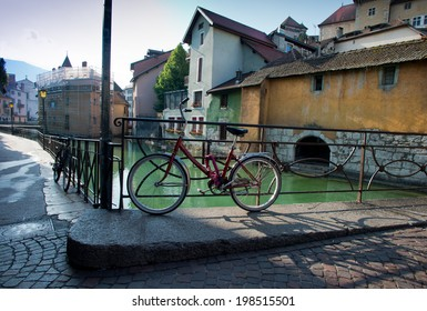 Vintage bicycle over old buildings on Annecy canal.