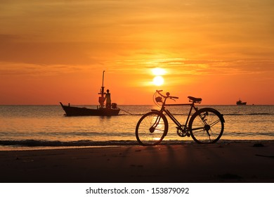Vintage bicycle parked on the hua hin beach with fishing boat background