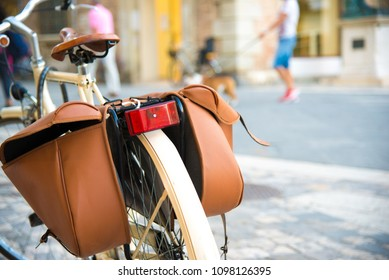 Vintage bicycle parking on the street. Bicycle with brown pannier bags for luggage.  Selective focus on foreground.  People with dog on background. Italy, Rimini. Street photo. Italian lifestyle.