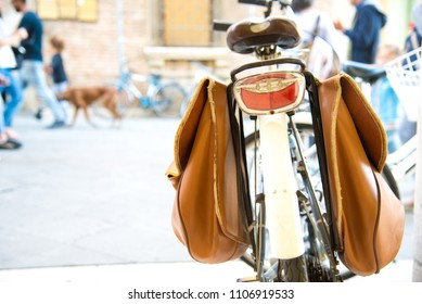 Vintage bicycle parking on the street. Street photo. Bicycle with brown pannier bags for luggage.  People with dog on background, selective focus on foreground.Italy, Rimini. Italian lifestyle
