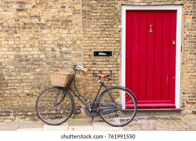 Vintage bicycle with retro wicker basket parked in front of a house brick wall next to a bright red door