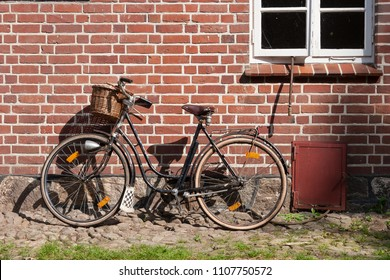Vintage bike leaning on a brick wall of a house