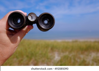 Vintage Binoculars with Compass Looking out over Sea Shore Towards Horizon