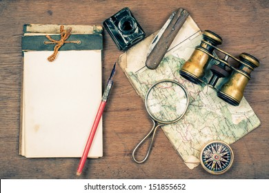 Vintage binoculars, notepad, compass, old map, ink pen, inkwell, pocket knife, magnifying glass on wooden background