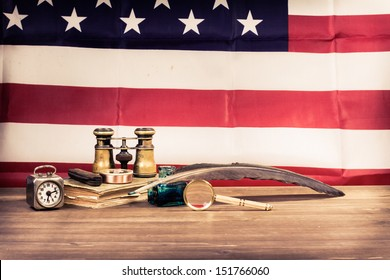 Vintage binoculars, quill pen, clock, compass, magnifying glass, old book, pocket knife, on table front USA flag background