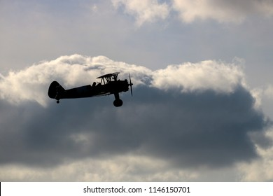 Vintage biplane silhouetted against an evening sky