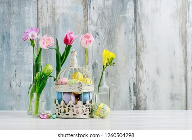 Vintage bird cage full of colorful Easter eggs and spring flowers in transparent glass bottles. Home decoration.