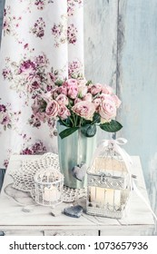 Vintage birdcage with cande and bouquet of pink roses in ceramic vase.