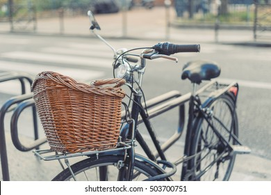 Vintage black bicycle with basket parked on the street. Retro wallpaper background. Shallow focus.