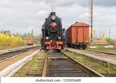 Vintage black steam locomotive train with wagons on railway station.