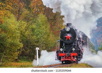 Vintage black steam locomotive train with wagons rush railway.