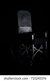 vintage black wheel chair on black background