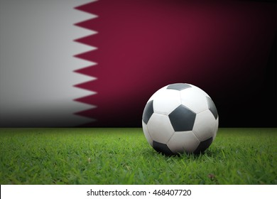 vintage black and white football ball on green grass has the national flag of Qatar backgroun.concept soccer football