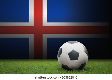 vintage black and white football ball on green grass has the national flag of Iceland background