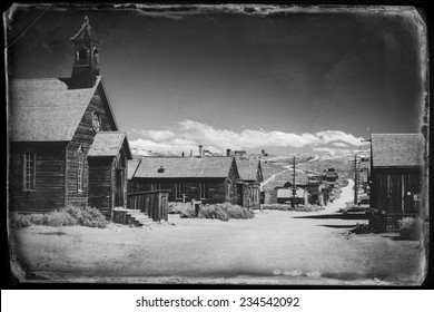 Vintage black and white old looking photo of empty streets of abandoned ghost town Bodie in California, USA in the middle of a day.