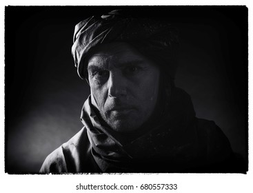 Vintage black and white photo of berber man in night light wearing turban with robe. Studio shot.