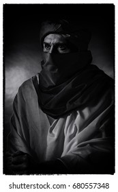 Vintage black and white photo of berber man in night light wearing turban with robe. Leaning on cane. Studio shot.