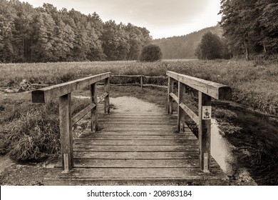 Vintage Black and White Wooden Bridge over a small Creek. Sepia Tone. Meadows and Countryside in Germany