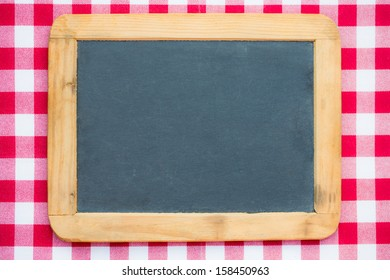 Vintage blackboard blank on gingham tablecloth background