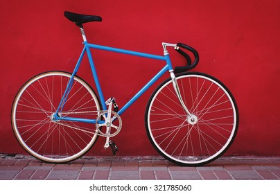 Vintage blue bicycle on red wall background.