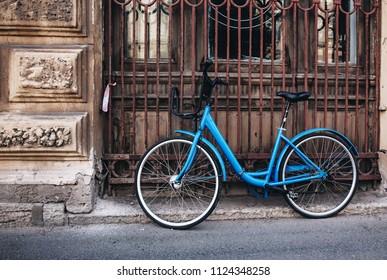 Vintage blue bike against old house, toned.