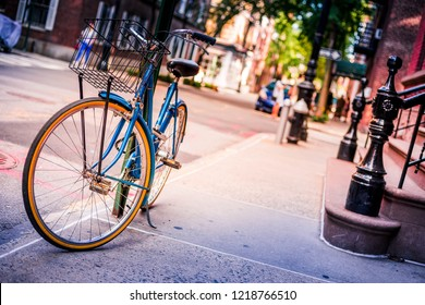 Vintage blue bike parked by a brownstone townhome in Brooklyn, New York