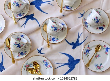 Vintage Blue Bird Tea Cups Teacups & Saucers on hand embroidered bluebird swallow tablecloth - flat lay - high tea party with gold teaspoons cutlery flatware