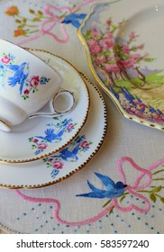 vintage blue bird teacup on embroidered table cloth with ribbons and chintz plate