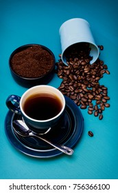 Vintage Blue Coffee Cup and Saucer with spilled Coffee and ground coffee in the background