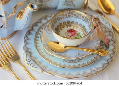 Vintage blue dinner plates, with pink rose tea cup and gold cutlery, wedding setting